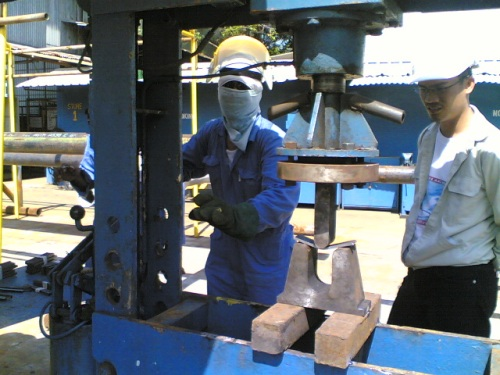 A Welder test specimen is being tested through a guided bend test while a Certified Sr. Welding Inspector is witnessing